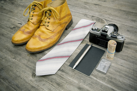 analogous: neourban hipster fashion travel with items handemade leather shoes, analog camera, notebook, pen, lighter, tie