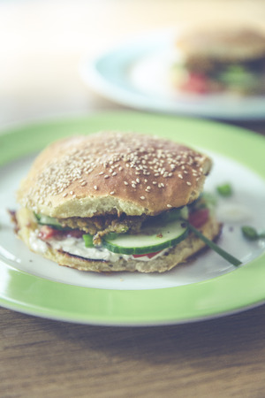 homemade veggie burger with cucumber, falafel, garbanzo, chickpea, tomato and wild celery Standard-Bild