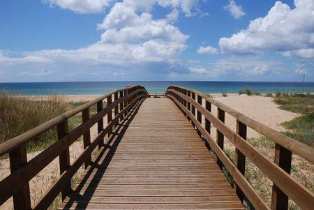 A footbridge to the sandy beach on a sunny day. photo