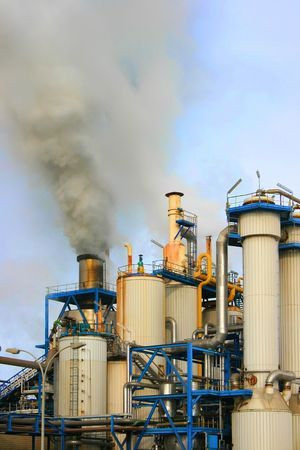Smoke rising from industrial sugar refinery plant photo