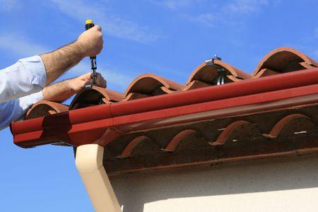 gouttière: �quipez installer le syst�me de goutti�re de pluie de PVC sur une maison Banque d'images