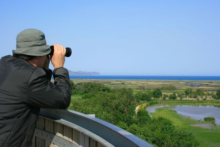bird watcher: Man looking through binoculars at a natural wetland area near the sea (Aiguamolls Emporda, Spain) Stock Photo