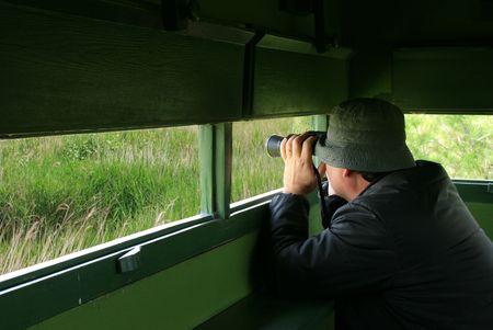birdwatcher: Man looking through binoculars in a birdwatching hideout