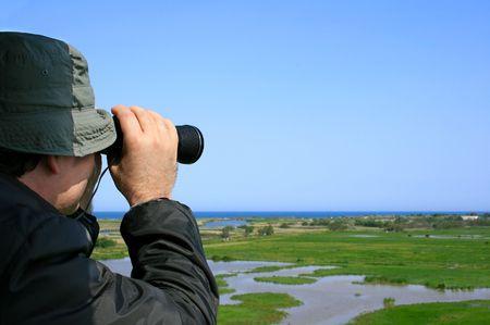 birdwatcher: Man looking through binoculars at a natural wetland area near the sea (Aiguamolls Emporda, Spain) Stock Photo