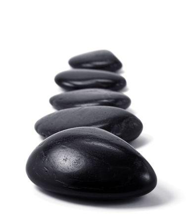 Black massage stones on white background photo