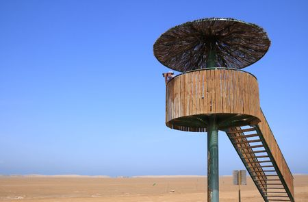 bird watcher: Man looking through binoculars in a birdwatching tower (Punta del Fangar, Ebro Delta,  Spain)