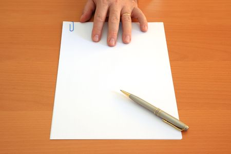 Male hand presents a blank document and a pen photo