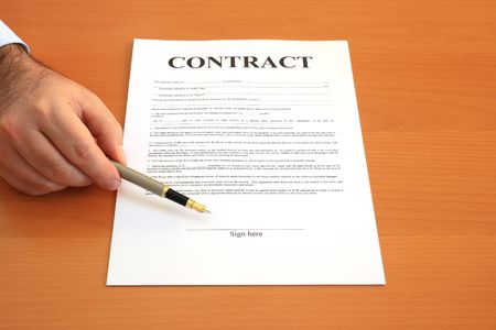 autograph: Male hand holding fountain pen pointing at signature place on a contract document (fictitious legal text)