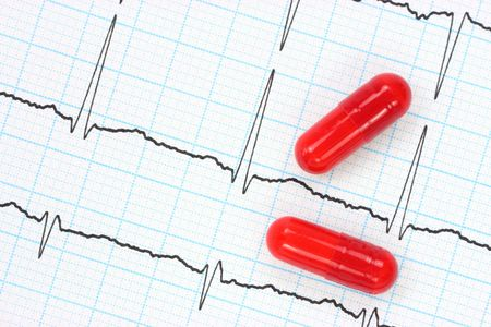 Two red capsules on electrocardiogram  photo