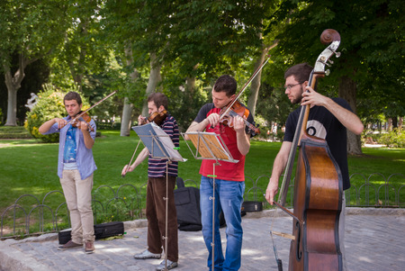 Young musicians playing different instruments perform on the street during the Madrid book fair in June 2011 報道画像