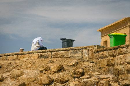 Egypt. Man sitting on the wall of the Islet of Agilkia.April 2019