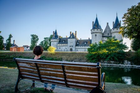 Woman sitting on a bench contemplating the castle of Sully sur Loire Stok Fotoğraf