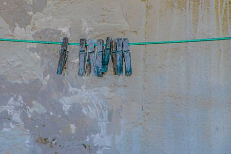 Old wooden clothespins hanging on the rope Standard-Bild