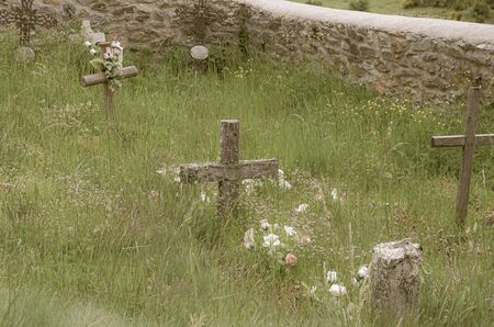 Crosses between the grass of a poor village cemetery