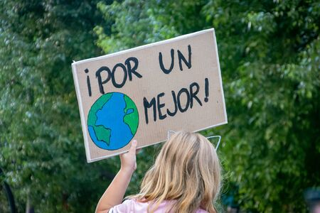 A girl raises a banner with the motto