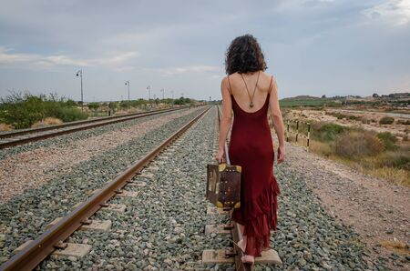 Woman with feet walking on the train track with a suitcase