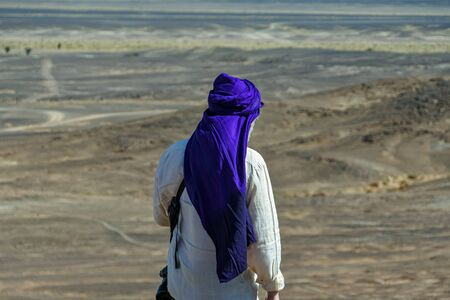 Portrait of man in white shirt and blue turban on his back in the desert of Morocco