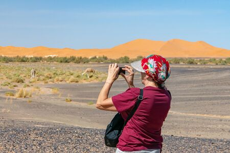Tourist woman with hat taking a picture in Morocco