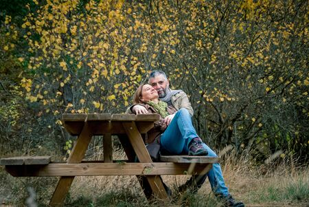 Couple of man and woman in love sitting at a wooden table in the countryside Archivio Fotografico