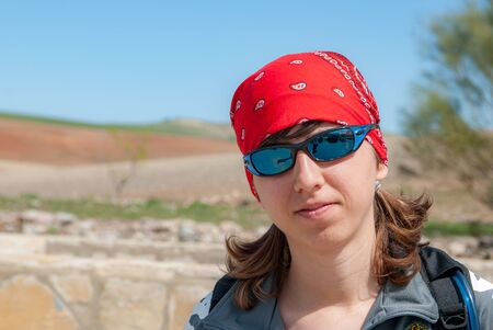 Portrait of young woman smiling with red headscarf and sunglasses