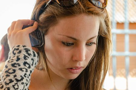 Portrait of thoughtful young woman listening to mobile