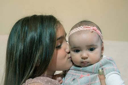 Older sister kissing her baby sister 版權商用圖片