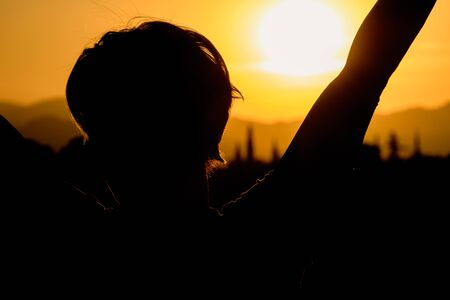 Woman with open arms raised on a sunset