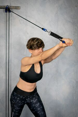 Young woman doing a toning exercise with pulley
