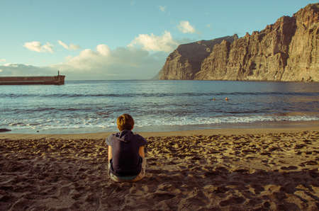 Girl sitting in front of the Los Gigantes Cliffs in Santiago del Teide, Tenerife island. Canary Islands. Spain