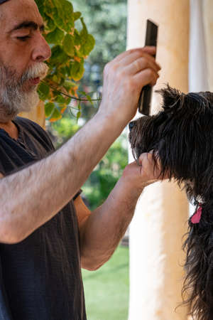 White man combs his black dog