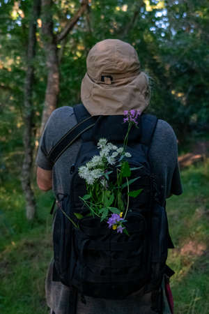 Man with cap and backpack full of flowers