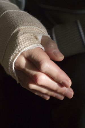 domestic violence: Woman holds bandaged wrist. Stock Photo