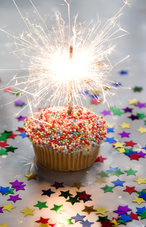 Cupcake with bright sparkler, on silver