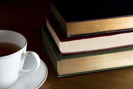 A cup of tea and stack of books photo