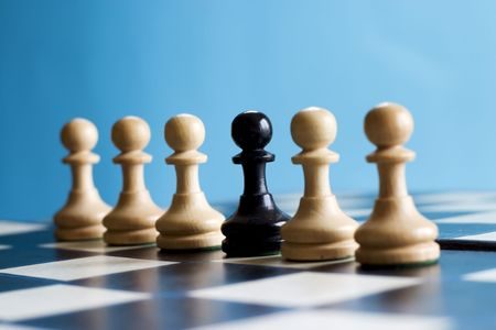 standoff: Row of pawns, one black pawn stands out Stock Photo