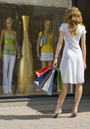 shoppingbag: Young attractive woman with paper bags looking at a shop window with mannequins Stock Photo