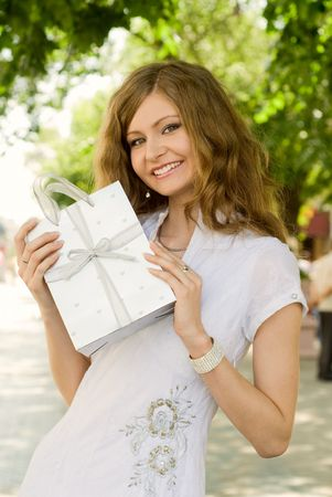 Beautiful young girl with gift bag in her hands outdoors photo