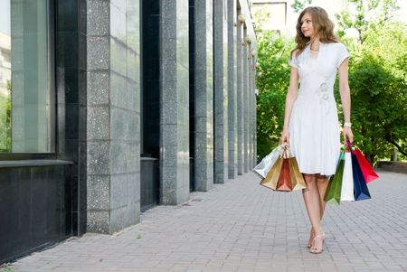 Woman walking along the shop windows with her bags photo