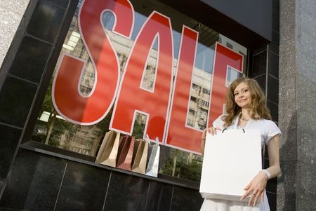 Woman holding blank white shopping bag in her arms near shop window with sale sign photo