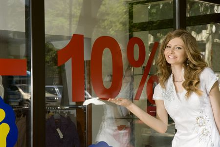Pretty woman shows 10% discount sign on a shop window photo