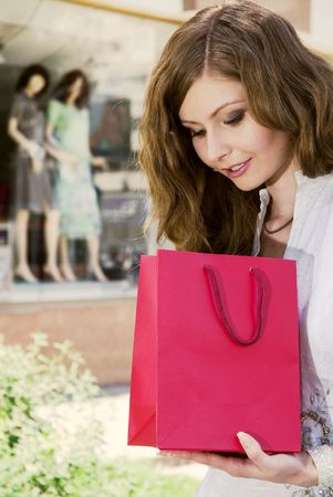 Woman with shopping bag looking what she had purchased photo
