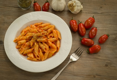 Penne pasta dressed with tomato sauce, garlic and oregano