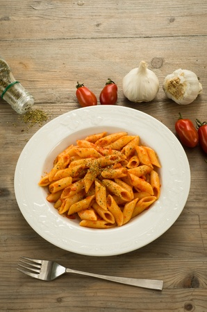 Penne pasta dressed with tomato sauce, garlic and oregano Stock Photo - 13756341