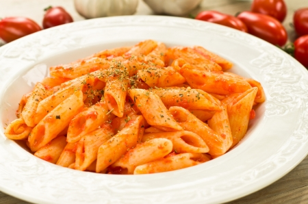 Penne pasta dressed with tomato sauce, garlic and oregano photo