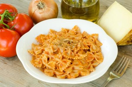 Farfalle pasta with tomato sauce and oregano photo