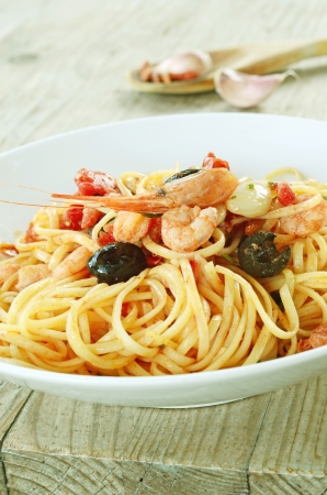 Linguine with tomato sauce, black olives and shrimps Stock Photo - 15948533