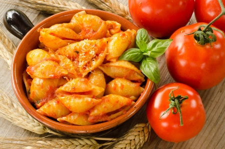 Conchiglie rigate with tomato sauce,basil and parmigiano cheese photo