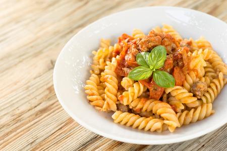 fusilli: Fusilli with pork sausage and tomato sauce, Italian Cuisine Stock Photo