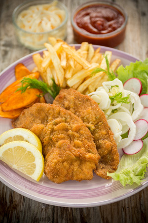 Fried beef cutlets with potato chips and fresh salad