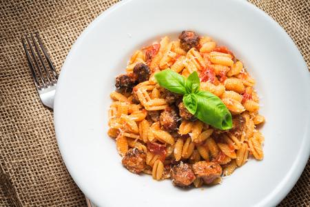 Malloreddus Campidanese, pasta sarda con salsiccia e salsa di pomodoro Archivio Fotografico - 86230179